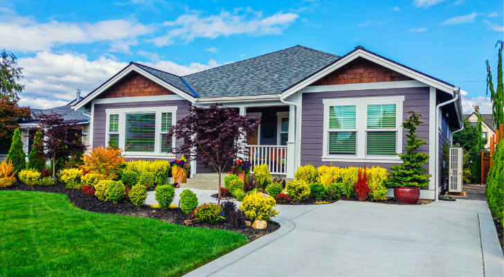 Image shows the facade of a home with a landscaped yard and driveway. SmartAsset analyzed data on home value change, housing costs, unemployment and more to find the most livable mid-sized cities in the U.S.