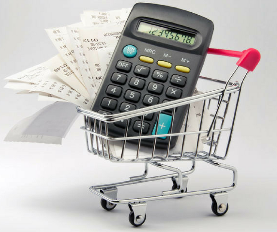 Calculator and receipt in shopping cart for grocery budget