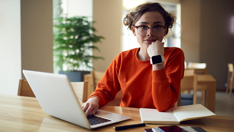 woman on laptop with notebook
