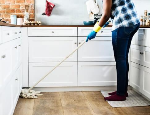 Man mopping up wet hardwood floor in apartment kitchen
